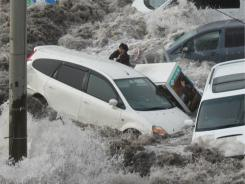 A reporter is swept by a surging tsunami wave at the port city of Kamaishi in northeastern Japan.
