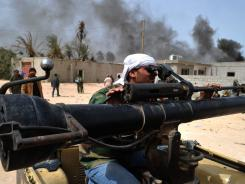 A Libyan rebel checks the sight on his weapon in Misrata, Libya, on Sunday.