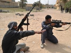 Libyan rebels prepare to fire toward a building where pro-Gadhafi forces are located in Misrata.