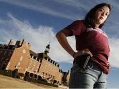Adrienne O'Reilly carries an empty gun holster at the Oklahoma State University to show support for guns on campus.