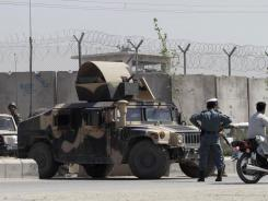 Afghanistan National Army (ANA) soldiers stand guard close to the perimeter wall of the Kandahar prison on Monday, after nearly 500 Taliban prisoners escaped.