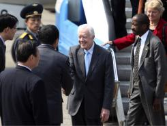 Former U.S. president Jimmy Carter, accompanied by his delegation members, is greeted upon arrival in Pyongyang.