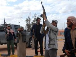 Libyan rebels pose with their weapons as they secure a road leading to Kabao in the district of Nalut near the border with Tunisia.
