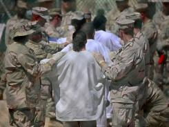 Guards stand on either side of a lineup of Guantanamo detainees, in white, to perform a search for unauthorized items.