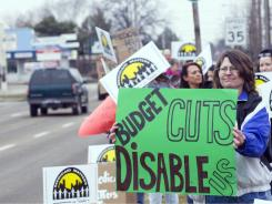Debra Custis of Eagle, Idaho, and others protest in February against proposed cuts in state funding for Medicaid.