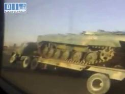 An image taken from video posted Wednesday on the Internet by Shaam News Network shows a line of Syrian army transporters carrying military tanks and armored vehicles.