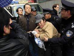 Chinese police officers detain a man Feb. 27 in Shanghai. Calls for pro-democracy protests in China prompted a sweeping crackdown.