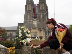 Virginia Tech sophomore Emily Parillo places a flower on a victim's memorial name stone on the Virginia Tech Drillfield in Blacksburg,Va., on April 16.