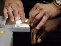 This July 26, 2010 file photo shows Senior Deputy Jerry Anttila fingerprinting an unidentified suspect  during the booking process at the  Arapahoe County Justice Center in Centennial, Colo.