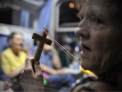 Polish pilgrims pray on a special train leaves for Rome, in Warsaw, Poland, late evening Friday.