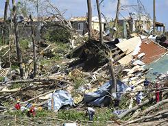 People look through the ruins in Ohatchee, Ala., last Thursday. Residents have begun digging out.