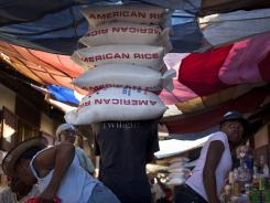 A man carries five sacks of rice at the La Saline Market in Port-au-Prince, Haiti, on April 21.