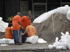 Inmates from an area prison fill sandbags Sunday in Cairo, Ill.