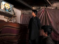 Customers watch a television featuring news of Osama bin Laden's death at a tea house in Kabul on May 2.