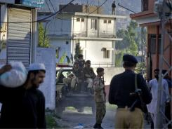 Pakistan army soldiers and police officers patrol past a house where it is believed al-Qaeda leader Osama bin Laden lived in Abbottabad, Pakistan.