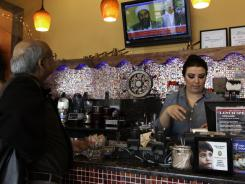Tamara Halees, manager at Assayad Restaurant in Dearborn, Mich., prepares a carryout order as a customer watches news of Osama bin Laden's death on television.