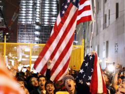 With the new One World Trade Center building in the background, a jubilant crowd reacts to the news of Osama bin Laden's death in New York.