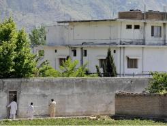 Pakistani security personnel measure a wall of Osama bin Laden's compound Tuesday in Abbottabad.