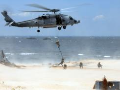 Navy SEALS conduct a fast-rope insertion demonstration from an MH-60S Sea Hawk helicopter onto a beach overlooking the Chesapeake Bay during a capabilities exercise at Naval Amphibious Base, Little Creek, Va., in 2009.