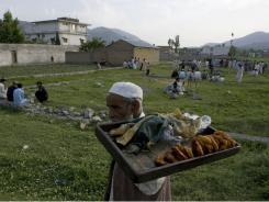 A Pakistani vendor sells traditional sweets close to the perimeter of the walled compound of a house where al-Qaeda leader Osama bin Laden was caught and killed in Abbottabad, Pakistan.