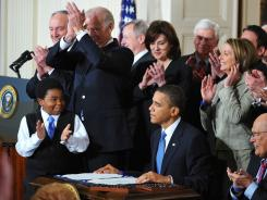 President Obama is applauded after signing the health care bill on March 23, 2010, in the White House.