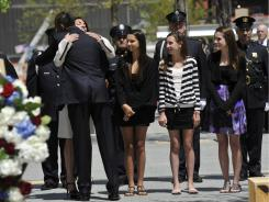 President Obama hugs Diane Wall, from Rumson, N.J., as her daughters and a family friend watch. Both families lost fathers on 9/11.