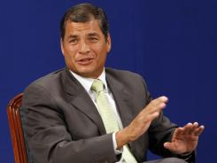 Ecuador's President Rafael Correa reacts after listening favorable reports about a referendum he proposed Saturday.