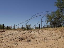 An old cattle fence, foreground, that used to mark the border, has been replaced by a border fence made to stop vehicle traffic, background, along a remote section at the U.S.-Mexico border near San Miguel, Ariz.
