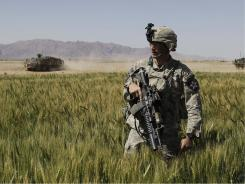 A U.S. soldier walks through a field on patrol last year in the Maiwand District of Kandahar province. In March, 49% said the war was going badly; now, 51% say it's going well.