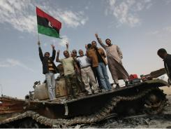 Libyan rebels hold up the old national flag as they stand on a destroyed government tank in the strategic oil town of Ajdabiya on March 29.
