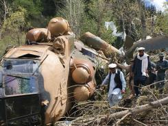 Afghan officials investigate the scene Wednesday after an Afghan Defense Ministry helicopter crashed when it hit a tree about 300 yards from the building housing governor Jamalludin Badar.