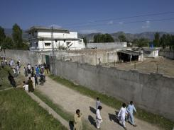 Media and local residents gather outside the house where al-Qaida leader Osama bin Laden was caught and killed, in Abbottabad, Pakistan.