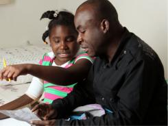 Ernst Leo goes over schoolwork with his daughter Therissa in their apartment in Miami. Leo's wife and oldest daughter were killed when their apartment building collapsed on them during the Haiti earthquake. Therissa was trapped for two days before she was rescued.