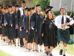 Charles Hightower, right, plays the bagpipes as he leads Spring Commencement graduate candidates toward their afternoon ceremonies for Auburn University at Montgomery on May 15, 2010, in Alabama.