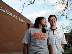 Shelton High seniors Sonali Rodrigues, right, and James Tate, left, pose outside of  their school in Conn.