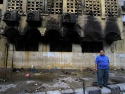 A man stands in front of a church set on fire during clashes between Muslims and Christians May 8 in the Imbaba neighborhood of Cairo.