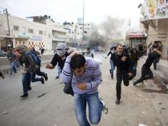 Palestinian protesters run on Sunday after tear gas was fired during clashes with the Israeli police.