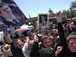 A crowd raises photos of Syrian President Bashar Assad as coffins of 11 soldiers and security force members are loaded into ambulances Saturday in Homs.