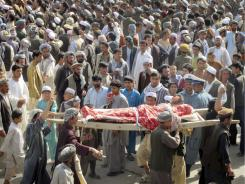 Afghans carry wrapped body of one of the four Afghans, killed in a NATO's raid, during an anti- U.S. demonstration in Taloqan, Takhar province, north of Kabul, Afghanistan on Wednesday.