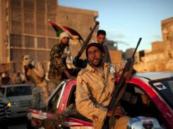 Rebel fighters act as security Thursday in downtown Benghazi, Libya.