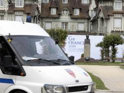 Police sit in front of a Deauville, France, hotel on Thursday prior to the Group of Eight summit next week.