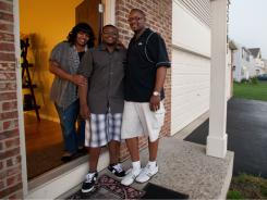 Karen and Kendall Taylor and their son Jeremiah, 15, stand on the front porch of their home in a new subdivision in Plainfield, Ill. They are among the many African Americans who have migrated from the city of Chicago to the suburbs.