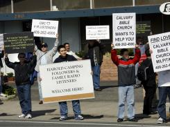 Members of the Calvary Bible Church of Milpitas appear Satuday at the closed Family Radio offices of Harold Camping in Oakland, Calif.