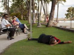 As tourists watch the sun go down May 13, a man sleeps near Waikiki Beach in Honolulu.