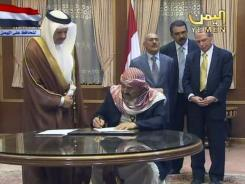 In this image taken from Yemen State TV on Sunday, Yemen President Ali Abdullah Saleh, standing behind 3rd from right, witnesses unidentified ruling party leaders signing an agreement for the president to step down in 30 days during a ceremony at the Presidential Palace in Sanaa, Yemen.
