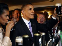 President Obama reacts after tasting a Guinness   at a pub as he visits Moneygall village in rural County Offaly, Ireland.