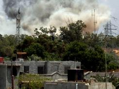 Smoke billows behind the trees following an air raid on the area of Tajura, east of Tripoli, as loud explosions rocked the Libyan capital on May 24, when NATO unleashed its heaviest blitz yet .