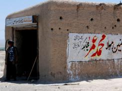 """Residents stand outside a shop with graffiti  reading """"leader of Muslims Mullah Mohammad Omar,"""" on May 8, in Pashin, Pakistan."""