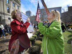 Peg Paulson, left , of Carmel, Ind., and Heather Pruett of Indianapolis disagree during a Planned Parenthood rally in March. A hearing is scheduled in June over a lawsuit involving family-planning funds.