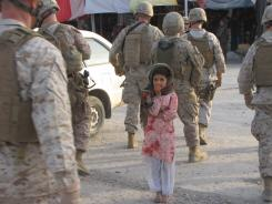 Marines on patrol pass a young Afghan girl in the village of Musa Qala.